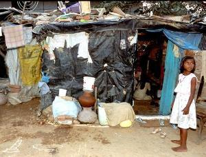 Young girl stands outside of a small lean-to