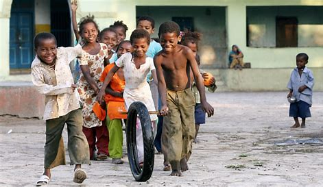 Group of children rolling a tire with a  stick.